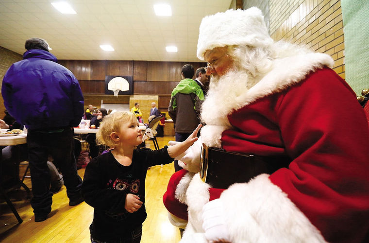 Paige Brandenburg, 2, feels Santa's beard Thursday at the Washington Neighborhood Christmas party at Immanuel Congregational United Church of Christ. (TH Photo/Mike Burley)