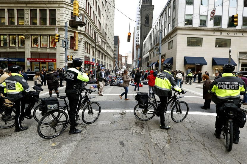 Pittsburgh police on bicycles block traffic from demonstrators protesting the deaths of two unarmed black men at the hands of white police officers in New York City and Ferguson, Mo. as they lay in the street during march through Pittsburgh on Thursday, Dec. 4, 2014. (AP Photo/Keith Srakocic)